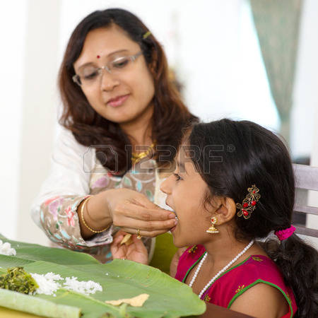 29384894-indian-family-dining-at-home-candid-photo-of-asian-mother-feeding-rice-to-child-with-hand-india-cult