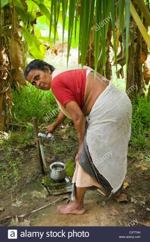 vertical-portrtait-of-an-indian-woman-collecting-clean-water-from-CXTT4H
